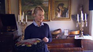 Kvinna står i muséum med dyna i handen.