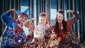 Kolme saamelaispukuihin pukeutunutta henkilöä