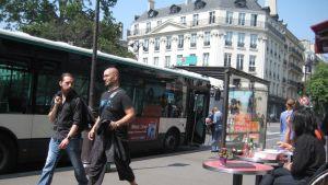 Pariisilaisbussi seisahtuneena pysäkillä, ihmisiä nousee bussiin ja kävelee ohi.