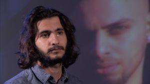 En ung mörkhårig man gråter, i bakgrunden projektion av ett ansikte