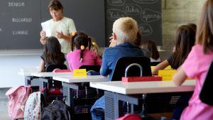 Pieniä koululaisia istuu pulpeteissaan ja kuuntelee luokan edessä olevaa opettajaa.