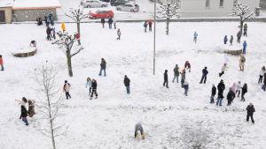 Koululaiset leikkivät koulun talvisella pihalla Aiglessa, Vaud'n kantonissa Sveitsissä.