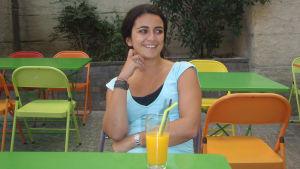 Nuori ranskalaisnainen värikkään ulkoilmakahvilapöydän ääressä mehulasin kanssa.
