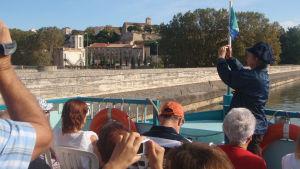 Matkailjoita kuljettava vene lipuu Canal du Midiä pitkin pikkukylän ohi Ranskassa.