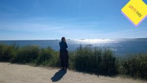 Nainen tuijottaa merelle.