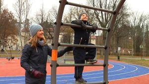 Tessi Czuryskiewicz med sin son Sebor som klättrar i lekställning i lekpark.