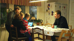 Familjen Johansson runt köksbordet och en datorskärm.