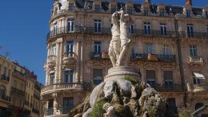 Veistos 'Kolme sulotarta' Montpellier'n keskusaukiolla, Place de la Comédiella, taustalla 1800-luvun kerrostalo.