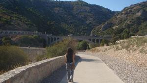 Nainen kävelee Hérault'n laaksoa reunustavalla kävelytiellä, taustalla vanhoja kaarisiltoja.