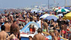 Ihmisiä ruuhkaksi asti Viareggion uimarannalla.