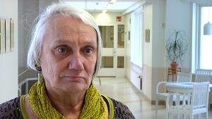 Psykiater Runa Nyholm står i en sjukhuskorridor. Det är Ekåsens sjukhsu i Ekenäs.