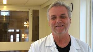 Mentalvårdare Seppo Salo står i en sjukhuskorridor på Ekåsens sjukhus i Ekenäs.