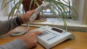 En hand lyfter telefonluren och ett nummer trycks.