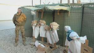 mansperson bredvid dockor i improviserad julkrubba