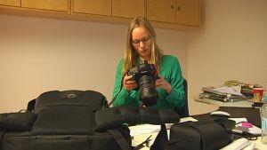 kvinna med kamera och kameraväska