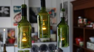 Kuvassa viinipulloista tehtyjä valaisimia