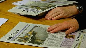 Nya Östis ligger på bordet, chefredaktörens fingrar tummar på tidningen.