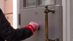 Närbild på en ytterdörr och en vante som knackar på