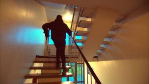 roland grankulla går uppför trapporna med sina kryckor