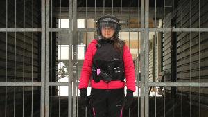 Kypärään ja turvavarusteisiin pukeutunut toimittaja portin edessä.