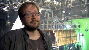 Regissören Antti-Jussi Annila i en inspelningsstudio. I bakgrunden syns en kuliss i metall.