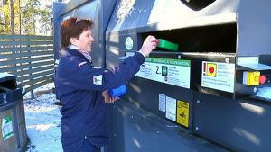kvinna sätter in plastburkar i återvinningskärl