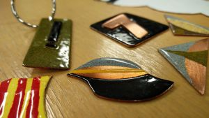 Små kopparbitar i olika former som emaljerats med olika färger på en brun bordsskiva.