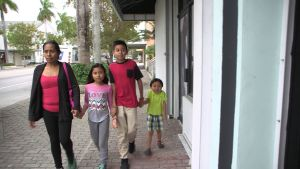 Maria, Eileen, William och Jason promenerar hand i hand på en gata.