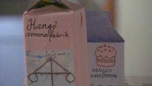 Gamla mjölkburkar som har fått nytt papper och fantasifulla texter på sig.