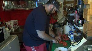 Kostas Chatziandreou skivar tomater i sitt kök.