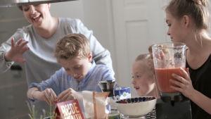 Barnen lagar bärsmoothies i köket.