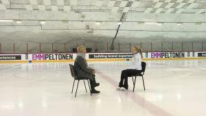 Konståkaren Emmi Peltonen och reportern Marianne Nyman sitter på varsin stol i en ishall med Emmi Peltonens namn längs sargen.