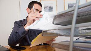 Mies selaa papereita toimistossa kynä kädessään.