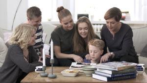 Joy och Ida Cedercreutz tittar på foton med Maria och barnen.