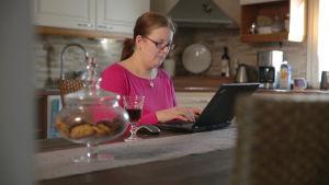 Tuhkimotarinoiden Katja kirjoittaa tietokoneella.