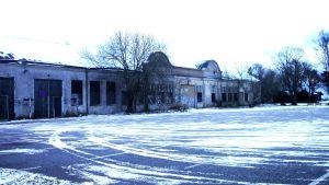 En gammal låg lång stenbyggnad i blått vinterljus, lite snö på marken.