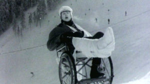 Hector laulaa laskettelurinteessä pyörätuolissa jalka isossa kipsissä.