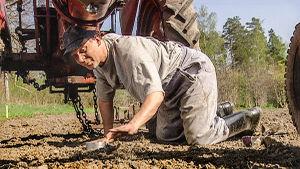 Mikko Roihiala kontillaan maassa traktorin edessä.