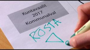 En text som säger Kommunalval 2017 och en hand som håller i en penna och skriver: Rösta!