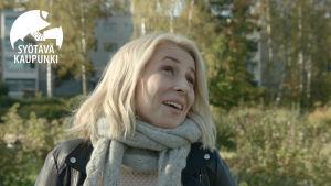 30-40-vuotias vaaleahiuksinen nainen katsoo yläviistoon. Hänellä on harmaa kaulahuivi kaulassaan, taustalla näkyy kerrostaloja ja keltalehtisiä puita ja pensaita.