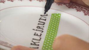 Textning med tusch på porslinstallrik.