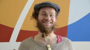 glad man med skägg, glasögon och hatt står framför en färggran vägg