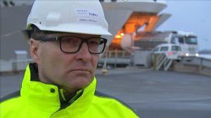 Hamndirektör i hjälm och gula kläder i Åbo hamn då Silja Galaxy just har anlänt.