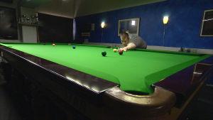 Snookerspelaren Heikki Niva stöter en boll på spelbordet.