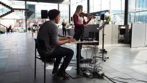 Viulisti Laura Ahola ja ääniteknikko Paavo Malmberg esittävät Tytti Arolan sävellyksen Kantapöydän suorassa lähetyksessä Musiikkitalon kahvilassa 26.4.2017.