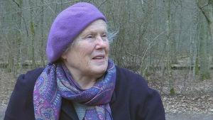 kvinna i lila basker och halsduk