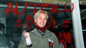 Näyttelijä Petteri Jamalainen seisoo Kotikadun bensiksen edessä kädessään spray-maalipurkki ja takanaan seinäkirjoitus