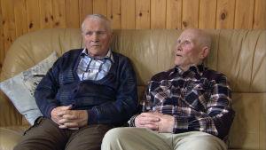 Eino ja Väino Kinnunen istuvat kotisohvallaan Suomussalmella.