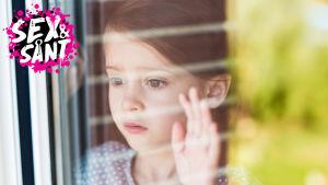 ett litet barn som ser oroligt ut ur fönstret med ena handen på fönsteret