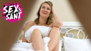 en kvinna som sitter i en säng naken täckt med täcke och ser nöjd ut